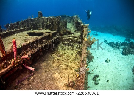 An underwater photographer examining the bow of the Willaurie ship wreck - stock photo