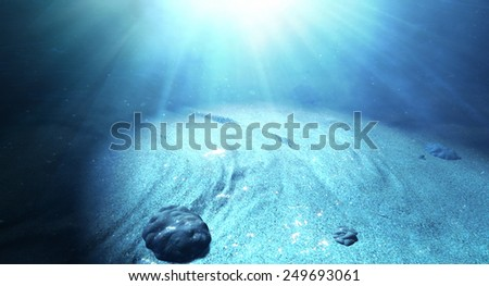 An underwater scene at the bottom of the ocean floor showing sand and emanating sunlight beaming through - stock photo