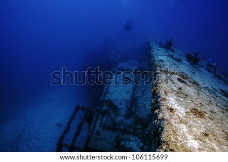 An underwater shipwreck laying on its side in the John Pennekamp State Park in Key Largo, Florida. With a technical diver swimming over it. The USCG Bibb. - stock photo