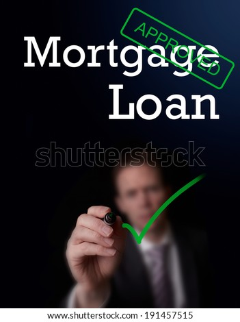 An underwriter writing Mortgage Loan approved on a screen. - stock photo