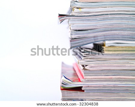 An uneven stack of magazines filling the frame from top to bottom with copyspace on left