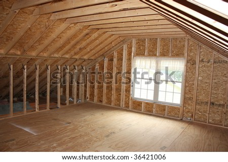 An unfinished 2nd floor with a window. - stock photo
