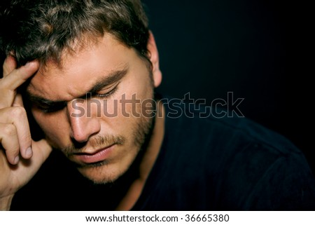 An unhappy depressed young man with a dark background - stock photo