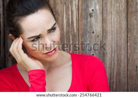 An unhappy, lonely depressed and sad woman sitting by wall. - stock photo