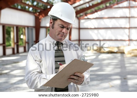 An unhappy looking construction inspector marking his checklist on a construction site. - stock photo