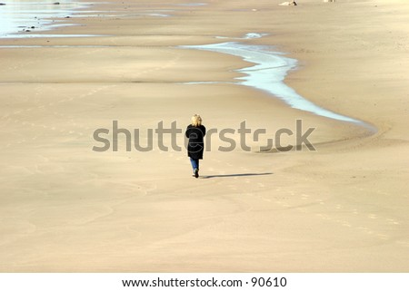 an unidentifable woman walks alone along a secluded beach in winter