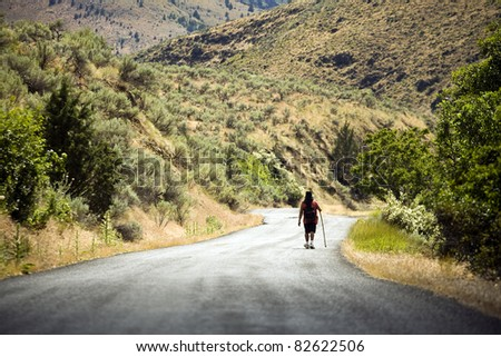 An unidentifiable man walks down a dirt road - stock photo
