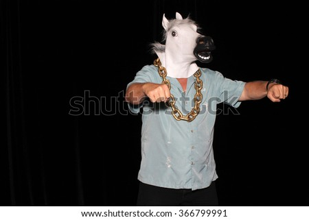An unidentifiable man wears a White Rubber Horse Head Mask, and a Gold Chain while in a Photo Booth with black velvet curtains as a background. With room for your text. Photo Booths are popular fun.