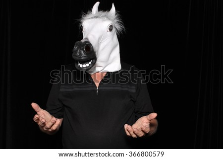 An unidentifiable man wears a White Rubber Horse Head Mask while in a Photo Booth. - stock photo