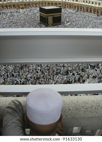 An unidentified muslim man looks on from third floor of Haram Mosque during hajj period in Mecca, Saudi Arabia. - stock photo