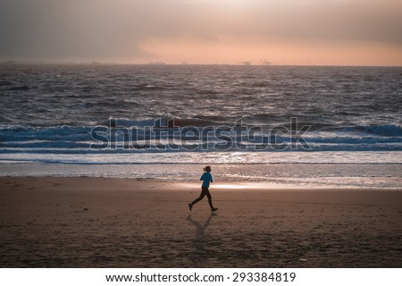An unidentified young woman running on a beach in the approaching sunset light, with oil rigs in the background  - stock photo