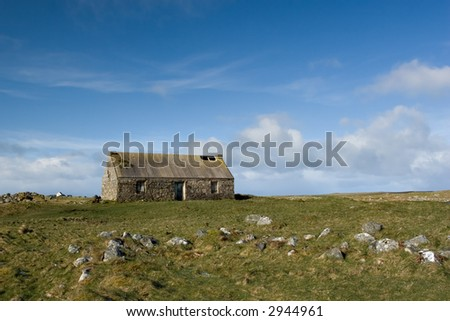 An uninhabited and boarded up house with holes in the roof in South Uist, Scotland