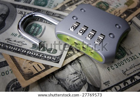 An unlocked padlock with the numbers 2009, on a pile of money. - stock photo