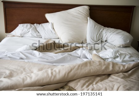 An unmade bed is strewn with white pillows. - stock photo