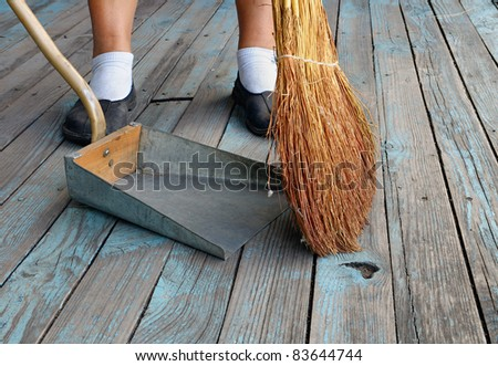 An unrecognizable person with a broom sweeping floor of the boards into dustpan. - stock photo