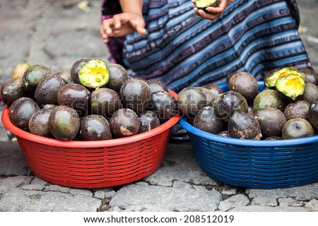 An unrecognizable woman sells avocado fruit at traditional weekly market in Chichicastenango (Chichi), Guatemala. - stock photo