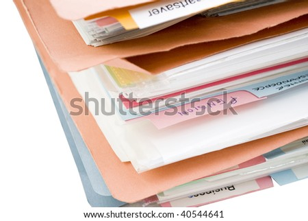 An untidy pile of folders, filled with papers, containing labeled dividers - the most legible divider is labeled 'Pension'.  Folders are made of cardboard and colored orange and blue.