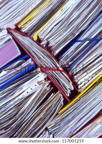 An untidy stack of un-filed office documents and papers - stock photo
