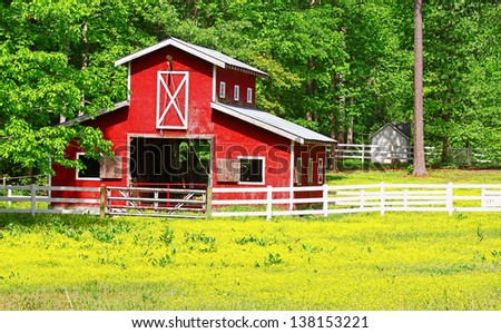 An unusual two story old red horse barn outside among the woods in a buttercup field - stock photo