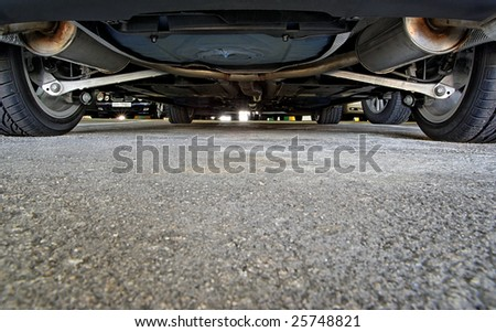 An unusual view of a car parking, from below a car. - stock photo