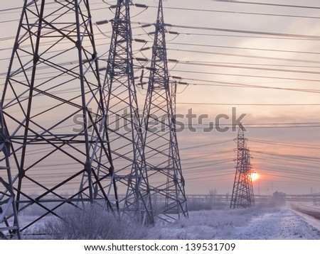 An unusual view of the high voltage on a snowy meadow - stock photo