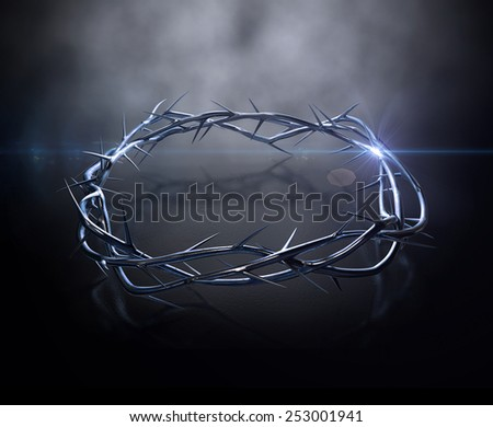 An upper view of a gold casting sculpture of branches of thorns woven into a crown depicting the crucifixion on a dark reflective surface spotlit by an eerie light - stock photo