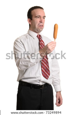 An upperclass man is disappointed about having to eat a corn dog, isolated against a white background.