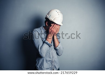 An upset blue collar worker is burying his face in his hands - stock photo