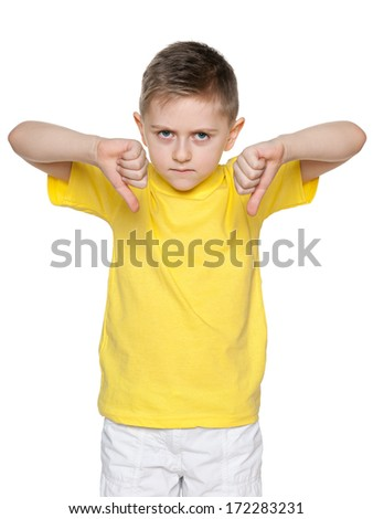 An upset boy in yellow shirt holds his thumbs down
