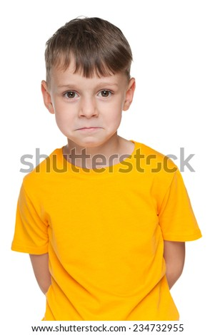 An upset little boy is standing against the white background