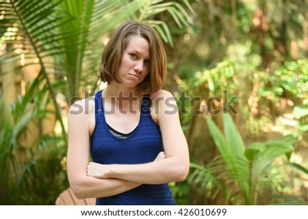 An upset young women with arms crossed and sad or powerless expression - stock photo