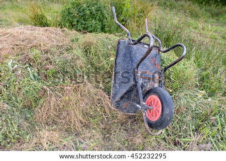 An upturned wheelbarrow on a compost heap of grass cuttings and weeds. - stock photo