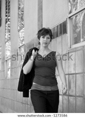 An urban businesswoman walking, slightly soft focus.