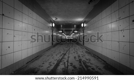 An urban pedestrian underpass with graffiti and low lighting making it an intimidating location. - stock photo