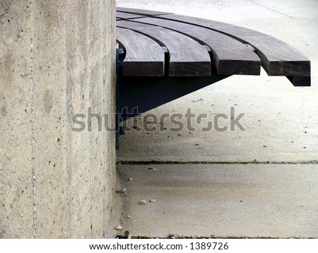 An urban plaza bench made of wood and concrete in strong light, shadow, and contrast. - stock photo