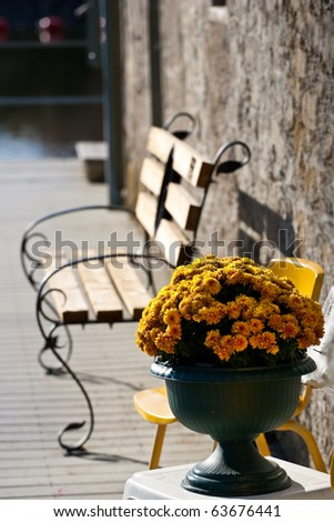 An urn full of bright yellow marigold flowers, in front of an empty bench. - stock photo