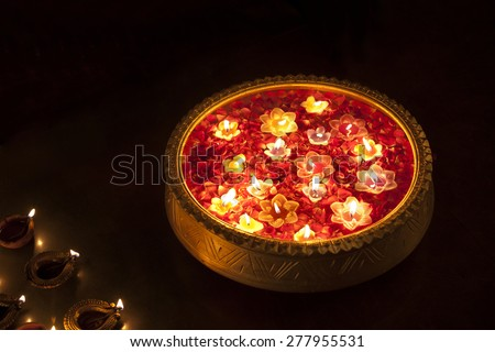 An urn with floating diyas - stock photo