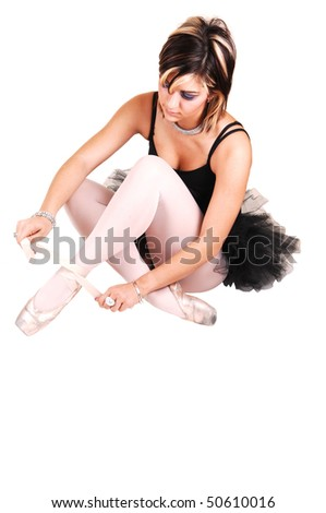 An very pretty young ballerina sitting on the floor in the studio and tying her ballet slippers in a black twill dress and white pantyhose, for white background.