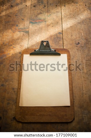 An vintage clipboard on a old wooden desk, with blank white paper. intentionally shot with stronger lighting on the upper half. - stock photo