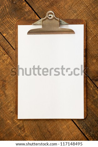 An vintage clipboard on a old wooden desk, with regular white blank paper. - stock photo