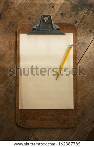 An vintage clipboard on a old wooden desk, with regular white blank paper. intentionally shot with stronger lighting on the upper half, so the message (to be inserted), stands out. - stock photo