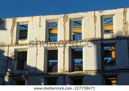 An white wall of an abandoned building with the sky in the background. - stock photo