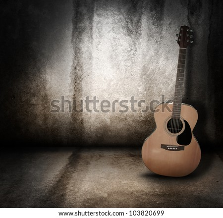An wooden acoustic guitar is against a grunge textured wall. The room is dark with a spotlight for your copyspace. Use it for a music or concert concept. - stock photo