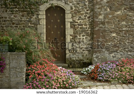 An wooden door to a church surrounded by flowers
