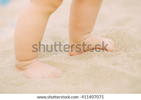 an 1 year old baby playing in the sands. This activity is good for sensory experience and learning by touch their fingers and toes through sand and enjoying its texture.