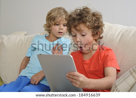 An 8-9 year old boy plays games on a touch screen tablet while his younger brother looks on. - stock photo