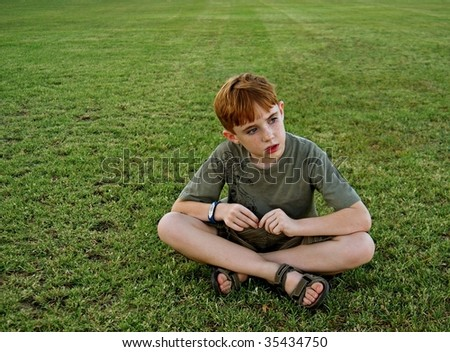 An 8-year-old boy sits on a grassy field and looks off out of frame - stock photo
