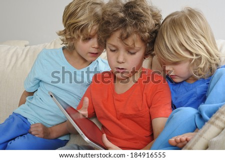 An 8-9 year old is playing a game on a touch screen tablet. His younger brothers are watching every move intently - stock photo