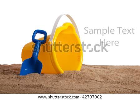 An yellow bucket and blue shovel on a sandy beach with copy space on a white background - stock photo