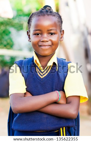 an young african girl in her blue and yellow school uniform and backpack, standing proud with her arms crossed.